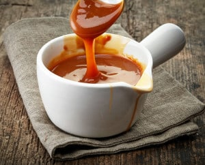 34662901 - bowl of melted caramel sauce on old wooden table